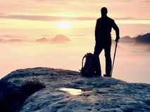 Man silhouette stay on sharp rock peak. Satisfy hiker enjoy view. Tall man on rocky cliff stock photography