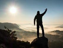 Man silhouette stay on sharp rock peak. Satisfy hiker enjoy view. stock photos