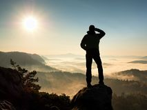 Man silhouette stay on sharp rock peak. Satisfy hiker enjoy view. Stock Photography