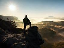 Man silhouette stay on sharp rock peak. Satisfy hiker enjoy view. stock photo