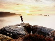 Man silhouette stay on sharp rock peak. Satisfy hiker enjoy view. Tall man on rocky cliff Royalty Free Stock Photo
