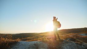 Man silhouette striving for success hand to hand walking tourist hiking adventure climbers sunset climb the mountain. Slow motion video. hiker sunlight on top stock video