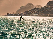 Man silhouette surfing with paddle board Stock Photos