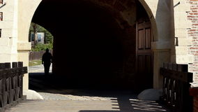 Man Silhouette on Tunnel. A man on shadow passes a gate of an old castle stock video footage