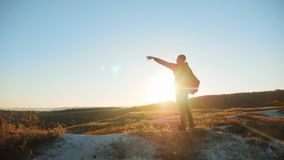Man silhouette walking tourist hiking adventure climbers sunset climb the mountain . slow motion video. hiker sunlight. On top win victory hill white rock stock video
