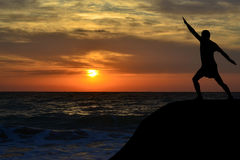 Man silhouette in a yoga pose on the shore at sunrise Stock Photo