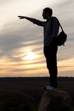 Man silhouetted against sunset pointing Royalty Free Stock Photo