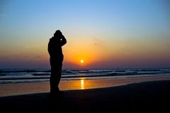 Man silhouetted against a vivid ocean sunset Royalty Free Stock Photo