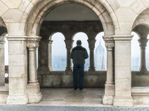 Man silhouetted within an arch of the Fisherman`s Bastian of Budapest, Hungary. Beyond the man is the city of Budapest and the Danube River. A turret of the St Royalty Free Stock Images