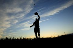 Man silhouetted by the sunset is just beginning. A man silhouetted by the sunset is just beginning catch ball with glove Royalty Free Stock Image