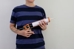 Man with silicone sealant and caulking gun in hands on white background. stock photography