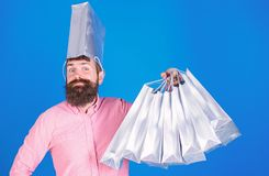 Man with silver bag on head going crazy about sales, fun and joy concept. Hipster in pink shirt with stylish beard doing. Shopping. Bearded man with present stock photos