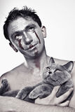 Man with silver makeup on his face and cat in  hands Stock Photography