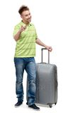 Man with silver suitcase pointing at something. Full-length portrait of man with silver suitcase pointing at something with forefinger, isolated on white royalty free stock image