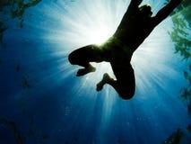 Man simning i havet med solstrålar som igenom skiner fotografering för bildbyråer