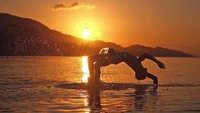 Man simning på den fantastiska solnedgångbakgrundsbanhoppningen och dykning till havet i ultrarapid 1920x1080 arkivfilmer