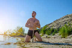 A man in a simple loincloth on the island is sitting with a stick. Toning royalty free stock photography