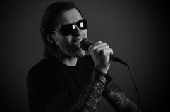 Man singer with microphone rock or metal. Black and white picture royalty free stock photography