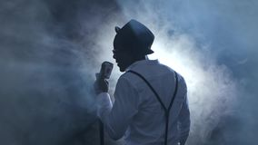 Man singer the view from the back in the smoke and white light sings into a microphone and dance. Black background stock video