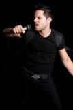 Man Singing. Sexy man singing into microphone Royalty Free Stock Image