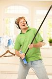 Man singing with broom. Smiling man singing with headphones, imitating playing guitar on broom at home Royalty Free Stock Photos
