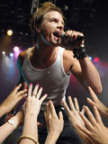 Man Singing Close To Adoring Fans. Young man singing on stage in concert with adoring fans reaching towards him Stock Photos