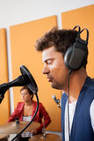 Man Singing With Female Drummer In Background. Young men singing with female drummer in background at recording studio Royalty Free Stock Photos