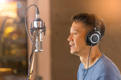 Man singing in front of recording microphone. Male singer wearing headphone during voice recording in studio,bokeh background Stock Photo