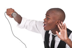 Man singing with his hand behing the ear. Young and beautiful black man singing with his hand behing the ear Royalty Free Stock Photo