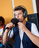 Man Singing While Holding Microphone. Young man singing while holding microphone in recording studio Royalty Free Stock Photography