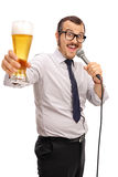 Man singing karaoke and holding beer. Vertical shot of a joyful young man singing karaoke on a microphone and holding a pint of beer isolated on white background Stock Photo
