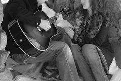 Man Singing Love Song to Fiance. Newly engaged couple in their 20's. Man is playing guitar, singing a love song to his betrothed. They are sitting on the steps Stock Images
