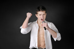 Man singing with microphone. Expressively man singing with microphone on dark background Royalty Free Stock Photography