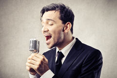 Man singing into a microphone Stock Image