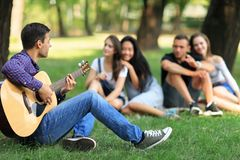Man singing song with guitar to his friends in park. On warm sunny day. Young people enjoy each others company, good weather and have fun. Weekend, vacation Royalty Free Stock Image