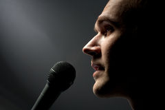Man singing to microphone Stock Photo