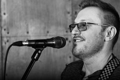 Man singing to microphone. Black and white portrait of man singing to microphone Royalty Free Stock Image