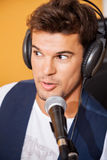 Man Singing While Wearing Headphones In Recording Studio. Closeup of young man singing while wearing headphones in recording studio Royalty Free Stock Images