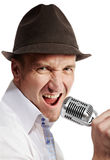 Man sings expressively into microphone. Man in the brown felt  hat sings expressively into the microphone Royalty Free Stock Photos