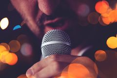 Man sings karaoke in a bar. At night with festive bokeh light effect, selective focus Royalty Free Stock Photos