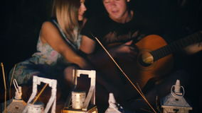 Man sings a song with a guitar to his girlfriend - the night in a field with candle lanterns.  stock video footage