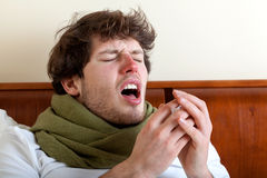 Man with sinus infection. Sneezing in bed stock images