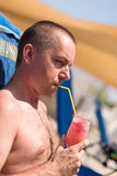 Man sipping a drink at a hotel swimming pool. Handsom man sipping a drink at a hotel swimming pool Stock Photography