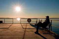 Man sit on bench on wharf construction and looking at sea. Sunny blue sky, smooth level Royalty Free Stock Photos