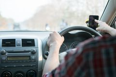 Man sit in the car hand is driving the car on the road. travel to He is looking to a road traffic route and listening to music. Happily stock image
