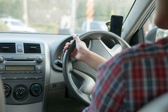Man sit in the car hand is driving the car on the road. travel to He is looking to a road traffic route and listening to music. Happily stock photo