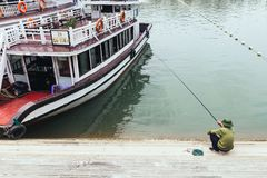 Man sit and fishing near tourist boat for going to Halong bay in background in summer at Quang Ninh, Vietnam Royalty Free Stock Photos