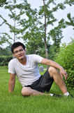 A man sit in meadow. A chinese young man sit in meadow Stock Photography