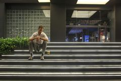 Man sit near shopping mall with coffee in evening royalty free stock photography