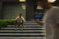 Man sit near shopping mall and looks at watch royalty free stock photo
